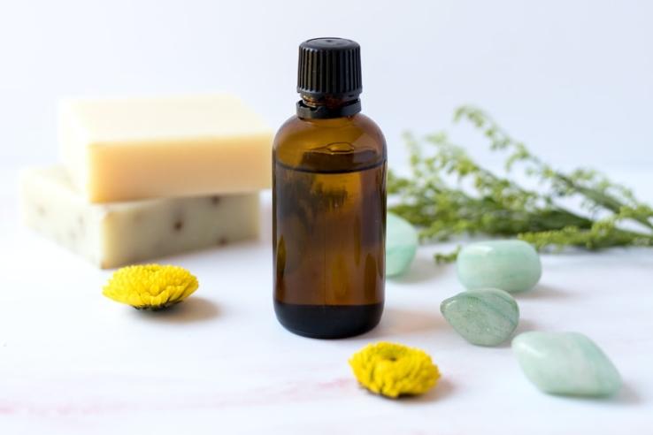 bottle-oil-yellow-flowers-green-rocks